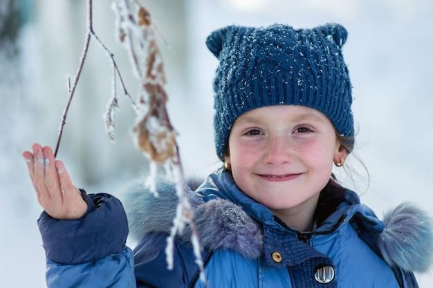 Inverno, menina feliz e sorridente segurando um galho congelado de uma árvore_