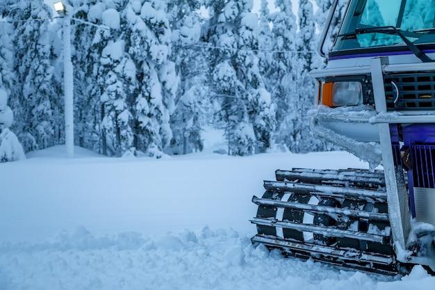 Inverno. muita neve. snowcat fica na orla da floresta