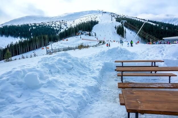 Inverno na eslováquia. estância de esqui jasna. encoberto. bancos e mesas de madeira vazios perto de uma pista de esqui