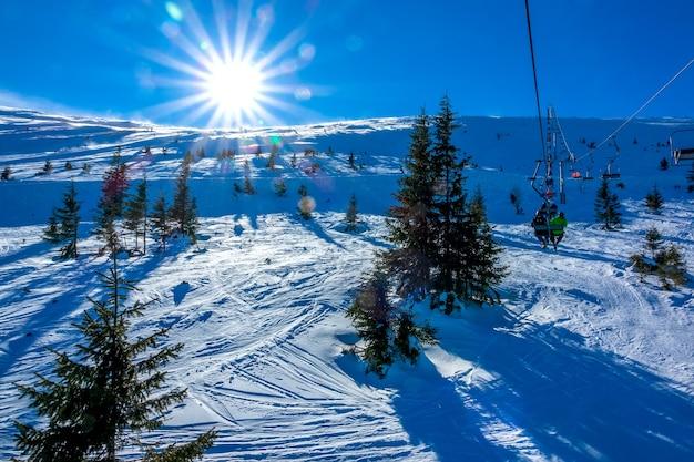 Inverno na eslováquia. estância de esqui jasna. sol forte sobre uma pista de esqui não equipada. vista do teleférico
