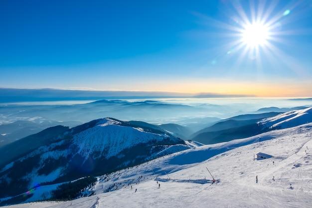 Inverno na eslováquia. estância de esqui jasna. vista do topo das montanhas cobertas de neve até a pista de esqui com esquiadores