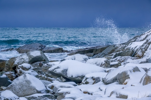 Inverno na noruega. costa rochosa coberta de neve do oceano. spray de água da onda de surf