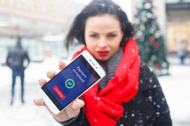 Inverno, natal, estilo de vida, conceito de moda - bela jovem sorridente de casaco preto e lenço vermelho, posando na cidade de inverno. morena atraente falando ao telefone no centro de negócios ao fundo