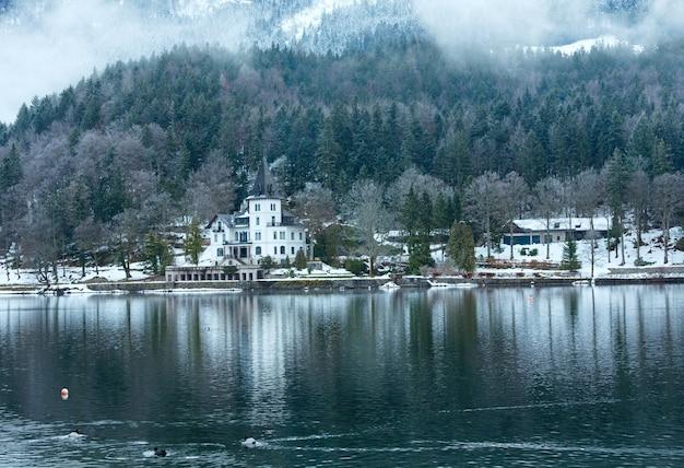 Inverno nublado com vista para o lago alpino grundlsee e casa branca (áustria)