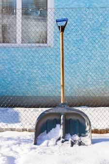 Inverno, perto da casa há uma pá para limpar o território da neve