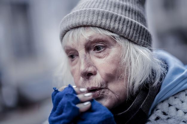 Inverno. retrato de uma mulher idosa triste soprando nas mãos enquanto sente frio