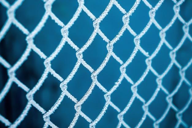 Inverno, uma grade de cerca coberta com gelo, um dia gelado de inverno
