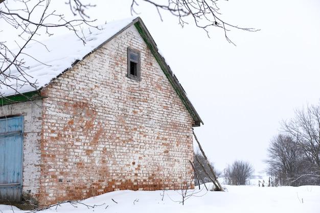 Inverno, velho celeiro em ruínas. muita neve ao redor