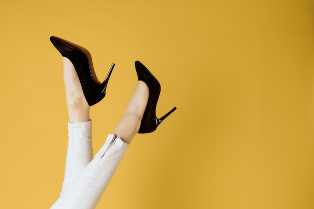 Invertido pernas femininas sapatos pretos atraente olhar amarelo compras na parede.
