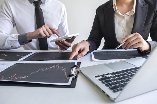 Investidor da equipe de negócios em reunião tendo planejamento e análise de cooperação de parceiros em projeto de marketing de negociação de investimento e apontando os dados apresentados e negociando uma bolsa de valores para lucrar.