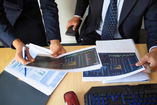 Investidor e comerciante discutindo dados estatísticos, segurando papéis com gráficos financeiros e caneta. foto recortada. trabalho de corretor ou conceito de negociação