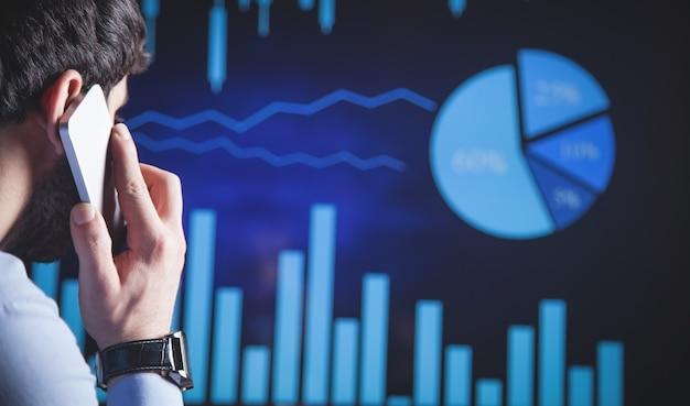 Investidor falando em smartphone em gráficos financeiros.