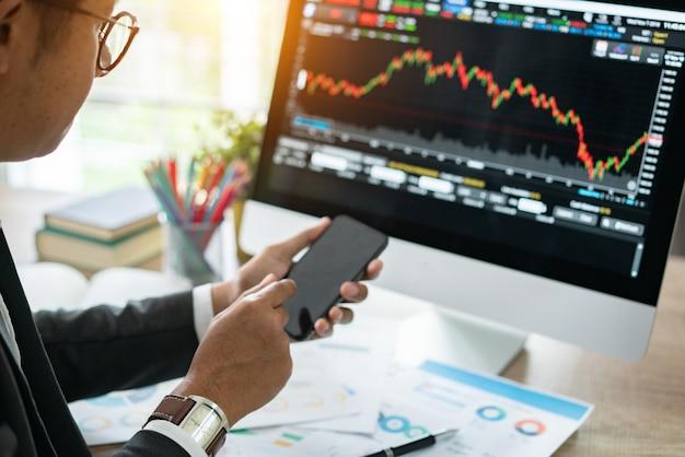 Investidor que presta atenção à mudança do mercado de valores de ação na tabuleta.