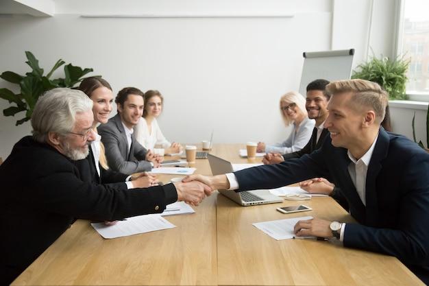 Investidor sênior, comprando, startup, handshaking, jovem, empreendedor, em, reunião grupo