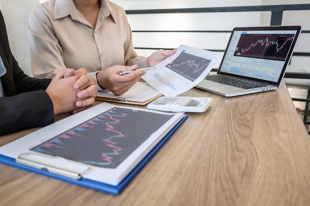 Investidora empresária em reunião tendo planejamento e análise de cooperação de parceiros em projeto de marketing de negociação de investimento e apontando os dados apresentados e negociando uma bolsa de valores para lucrar.