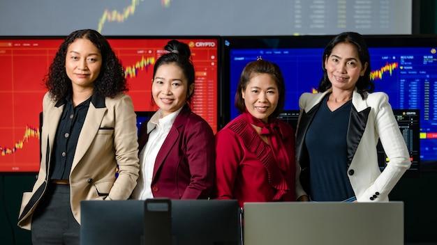 Investidora profissional bem-sucedida, investidora, sorriso, olhar para a câmera na frente do monitor do computador