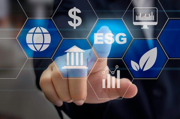 Investimento ambiental, social e de governança (esg) o crescimento organizacional sustentável é uma ideia de negócio. a mão de um homem toca a palavra esg em uma tela virtual.