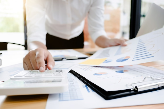 Investimento de análise de mulher de negócios executa documento de dados e calcula um número de avaliação