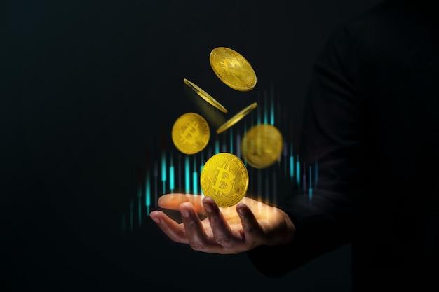 Investimento de dinheiro no conceito de moeda de criptografia. bitcoin dourado flutuando sobre a mão de um comerciante. gráfico do mercado de ações.