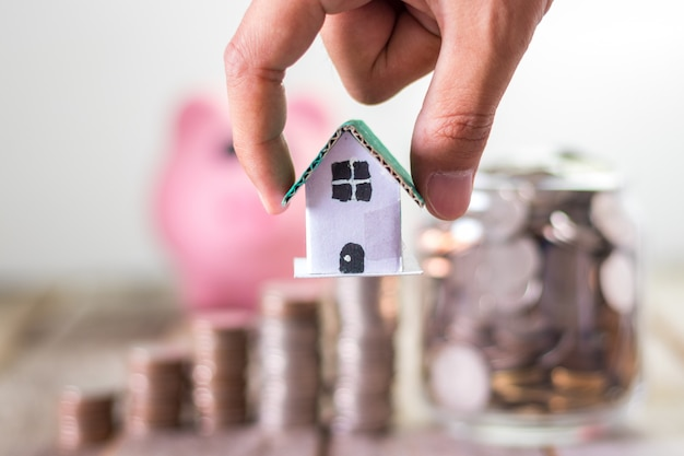 Investimento em casa, economizando dinheiro para hipotecas, moedas em um frasco de vidro na mesa de madeira