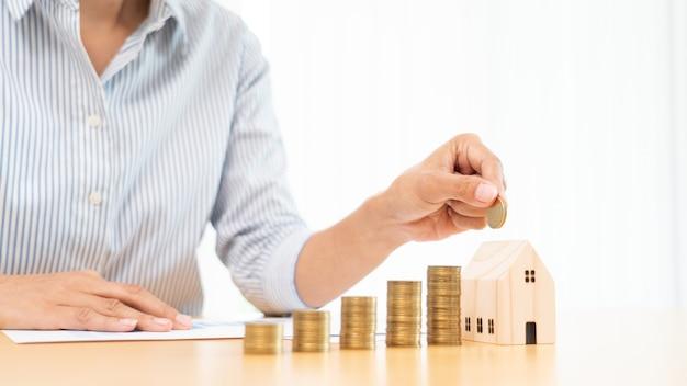 Investimento em propriedade e conceito financeiro de hipoteca de casa, mão de um empresário que está empilhando moedas