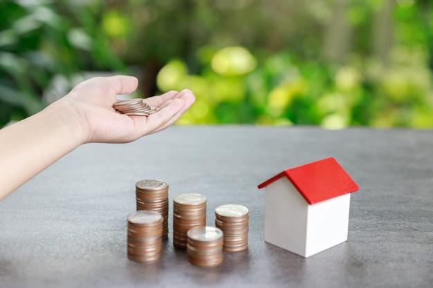Investimento em propriedade e conceito financeiro de hipoteca de casa, rapaz asiático colocando dinheiro para a pilha de moedas com o modelo da casa sobre fundo verde.