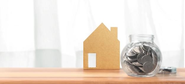 Investimento em propriedade e pilha de moeda do dinheiro do conceito financeiro da hipoteca da casa. casa de negócios