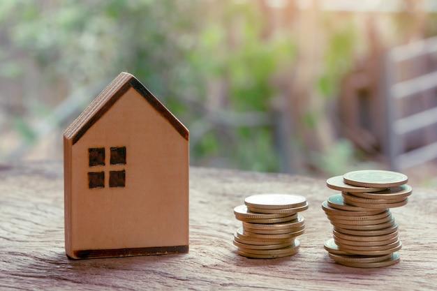 Investimento imobiliário, casa e pilha de moedas. conceito de hipoteca imobiliária