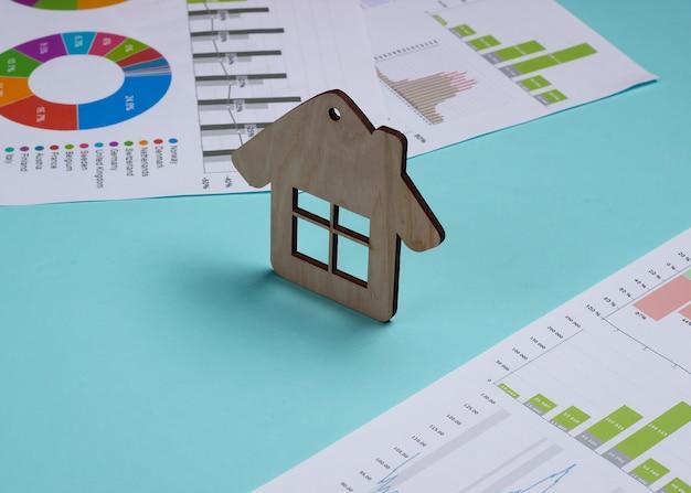 Investimento lucrativo. análise de mercado. comprando um imóvel. minifigura, gráficos e tabelas de casa em fundo azul pastel