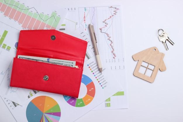 Investimento lucrativo. análise de mercado. comprando um imóvel. minifigure de casa com chave, bolsa, notas de dólar, gráficos e tabelas. negócios e finanças
