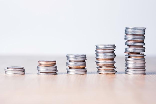 Investimento no mercado de ações e conceito de lucro empresarial, gráfico crescente de moedas de prata e bronze na mesa.