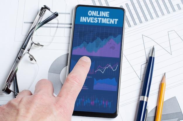 Investimento online. um homem está segurando um smartphone com um aplicativo móvel com tabelas e gráficos.