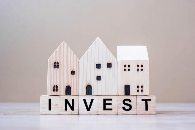 Investir blocos de cubo com modelo de casa de madeira no fundo da tabela.