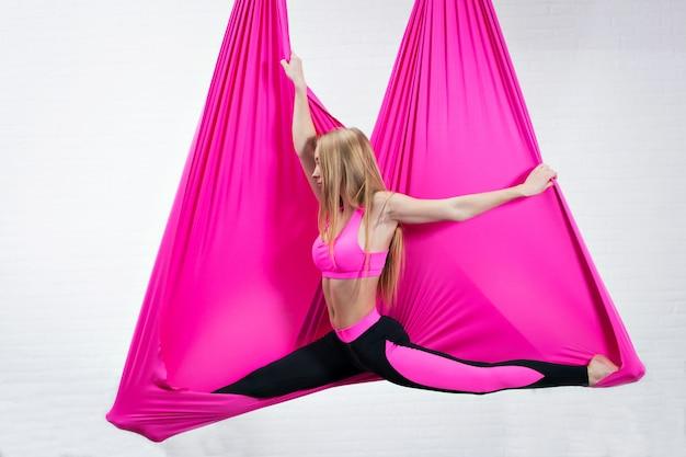 Ioga antigravidade linda garota em uma rede de seda rosa