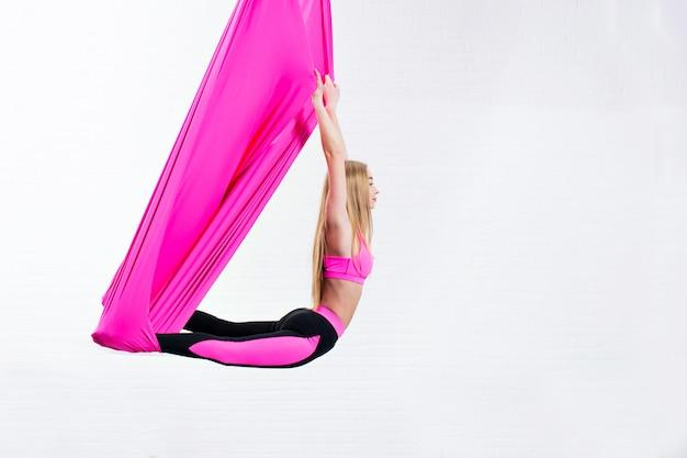 Ioga antigravitante da moça bonita em uma rede de seda cor-de-rosa ao fazer.