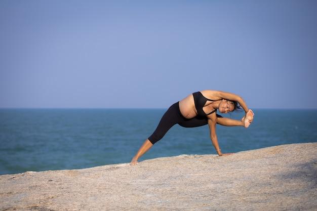 Ioga asiática da mulher gravida nas horas de verão do sol da praia