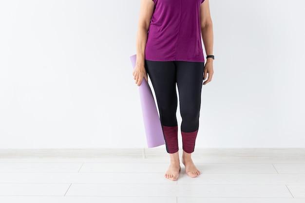 Ioga, conceito de peopel - close-up de uma mulher segurando o tapete depois de uma aula de ioga em fundo branco com