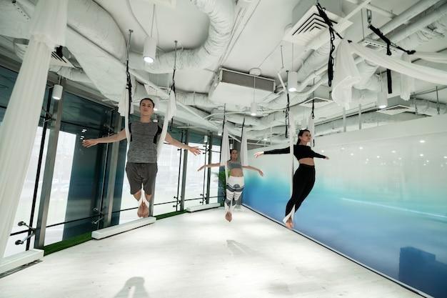 Ioga da antigravidade. homem e duas mulheres vestindo roupas esportivas, sentindo-se livres enquanto praticam ioga antigravitacional