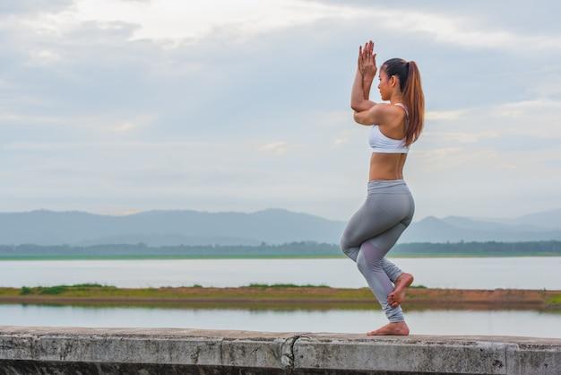 Ioga de treino, jovem mulher fazendo exercícios de ioga na parede em belos lagos de montanha