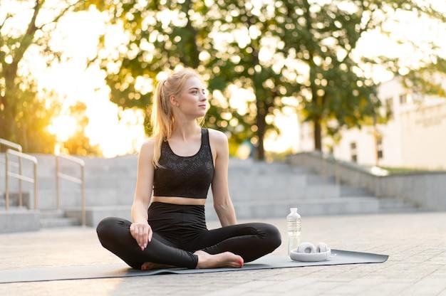 Ioga e meditação na cidade moderna mulher caucasiana relaxa posição de lótus sentar-se tapete de ioga ao ar livre parque de verão em piso de concreto jovem adulto apto feminino relaxando após o treino de ioga siddhasana