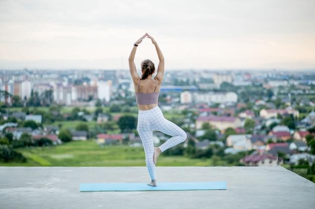 Ioga em alta altitude com a cidade grande no fundo, mulher sorridente sentada em pose de ioga no fundo da cidade incrível, mulher meditando ioga e aproveitando a noite ensolarada, a mulher faz ioga.