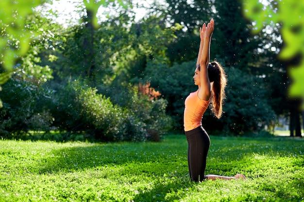 Ioga. jovem mulher praticando ioga ou dançar ou esticar na natureza no parque. conceito de estilo de vida de saúde