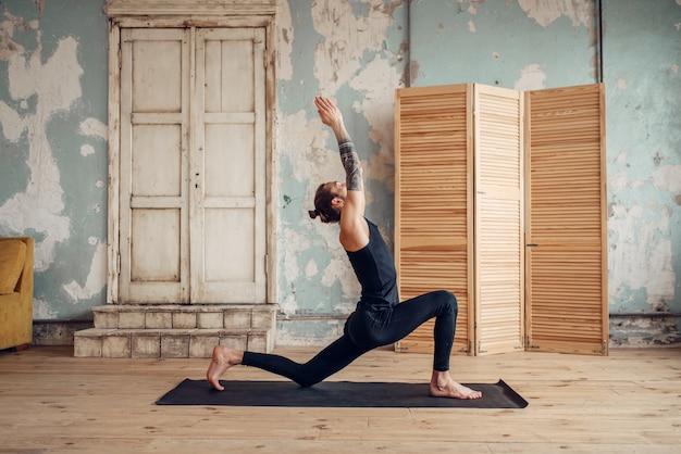 Ioga masculina com tatuagem por lado, fazendo exercício no ginásio com interior do grunge. treino físico dentro de casa