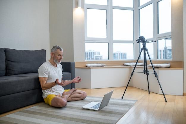 Ioga online. um homem maduro de camiseta branca fazendo um tutorial de ioga online