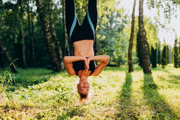Ioga praticando da mosca da jovem mulher do close up no cair da árvore de cabeça para baixo.