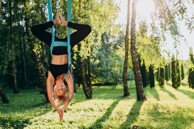 Ioga praticando da mosca da menina na árvore pendura de cabeça para baixo.