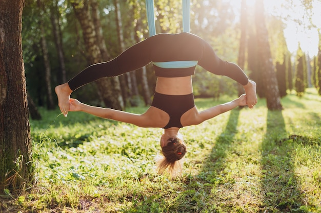 Ioga praticando da mosca da mulher na árvore que espalha seus pés separados distante.