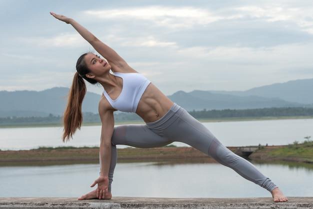 Ioga praticando da mulher bonita pelo lago com montanha.