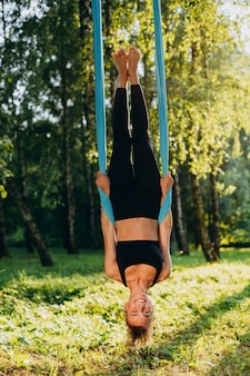 Ioga praticando de sorriso da mosca da mulher na árvore pendura de cabeça para baixo.