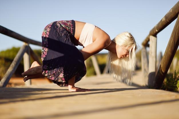 Ioga praticando fêmea caucasiano na ponte de madeira.